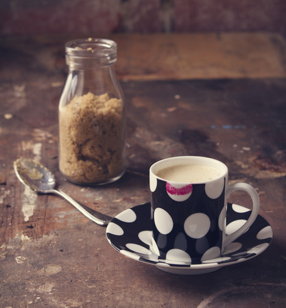 Lipstick on coffee cup in rustic cafe or art studio setting Stock Photo