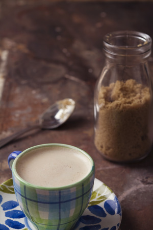 Cute handmade coffee cup and raw sugar in glass bottle Stock Photo