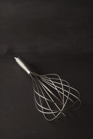 Creative still life of a single whish kitchen utensil on blackboard background