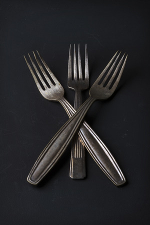 tarnished: Conceptual still life of three vintage silver metal forks Stock Photo