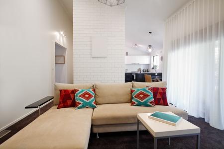 cortinas rojas: Sof� de la sala moderna y mesa de caf� con la cocina en el fondo Foto de archivo