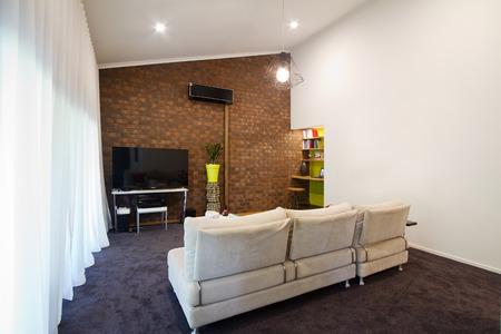 living unit: Renovated 70s retro exposed brick wall apartment living room Stock Photo