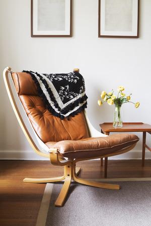 silla: Cuero bronceado silla retro vintage dan�s y mesa con jarr�n de flores Foto de archivo