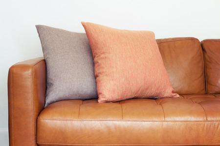 2 つのリネン クッションの日焼けの革のソファのクローズ アップ