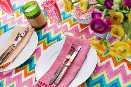 Bright colorful table setting with multi colored chevron pattern tablecoth