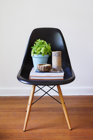Contemporary black plastic dining chair with a plant, books and candles