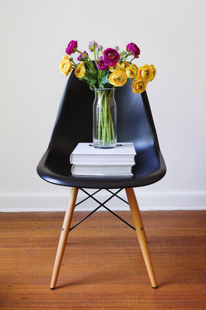 vintage chair: Contemporary black dining chair with vase of yellow and purple flowers