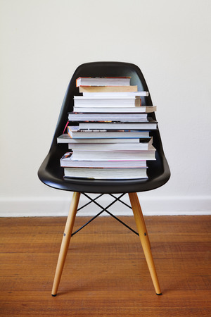 Contemporary black dining chair with stacked high with books