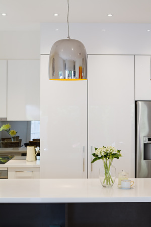 Modern kitchen renovation with hanging chrome penant light Stock Photo