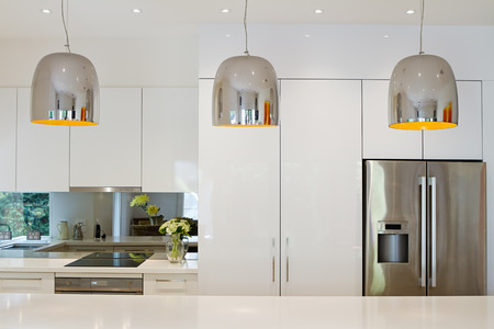 stainless steel kitchen: Contemporary pendant lights hanging over kitchen island bench