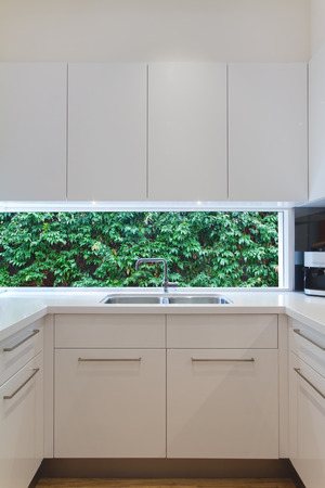 new kitchen room: Residential contemporary kitchen sink with low window showing a green hedge Stock Photo