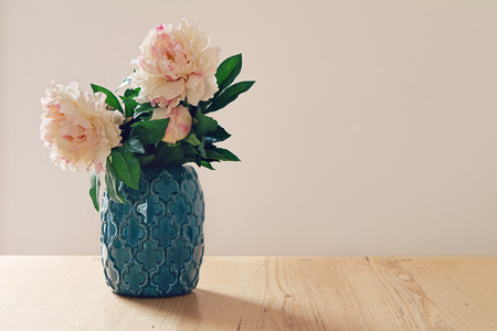copy room: Blue moroccan style vase of large white and pink flowers in pastel hues