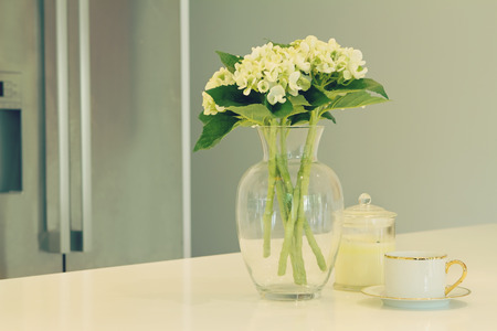 hues: Glass vase of white flowers, teacup and candle in a kitchen with blurred fridge behind in soft green hues Stock Photo