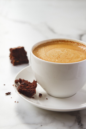 Crumbling chocolate brownie on espresso coffee cup cappucino or latte saucer Stock Photo