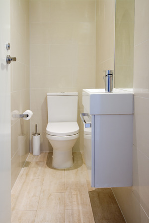 Contemporary fully tiled powder room toilet in a new renovated home photo