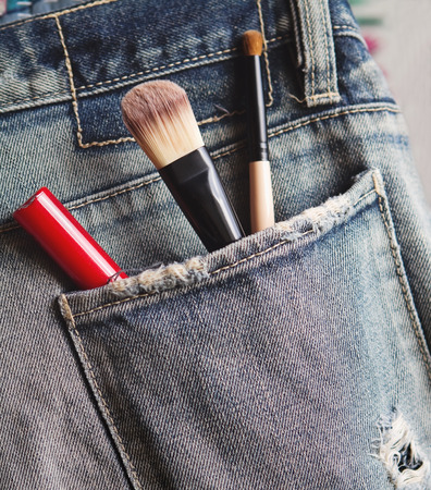 worn jeans: Make up tools and lip gloss in rear worn jeans pocket Stock Photo