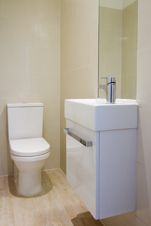 Angled view of newly renovated fully tiled bathroom toilet and basin photo