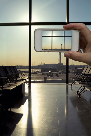 Cell phone camera taking a photo from the departure lounge waiting area at a modern airport