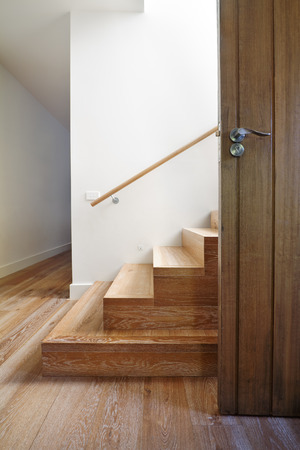 wooden stairs: Modern staircase of oak wood beside front door in contemporary home