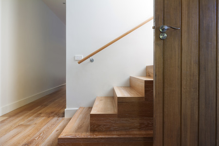 stairs interior: Modern staircase of oak wood beside front door in contemporary home horizontal