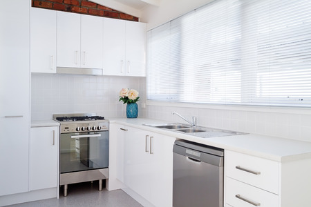 kitchen: New white kitchen and appliances in a renovated villa unit Stock Photo
