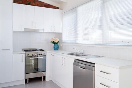 New white kitchen and appliances in a renovated villa unit Archivio Fotografico