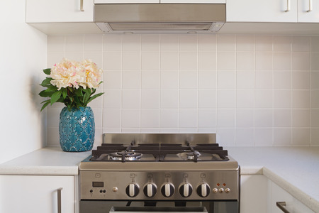 stainless steel kitchen: Close up of kitchen oven and tiled splashback in contempory apartment Stock Photo