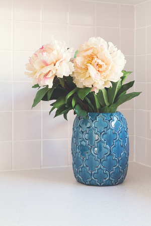 kitchen bench: Blue moroccan vase with large white flowers on kitchen bench
