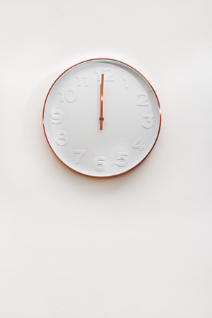 12 o'clock: Modern copper and white decorative wall clock on a white wall Stock Photo