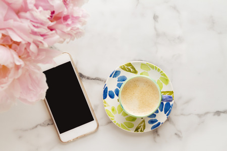 lay: Overhead of coffee, mobile phone and flowers on a marble background