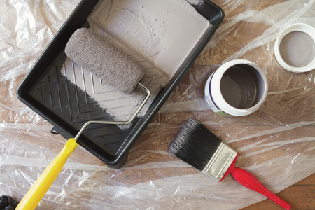 Overhead view of home painting equipment brush roller tray and paint pot