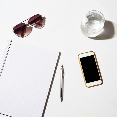anteojos de sol: Gafas de sol teléfono agua y bloc de notas en una mesa blanca desde arriba