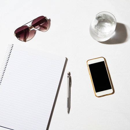 overhead: Sunglasses water phone and notepad on a white table from overhead