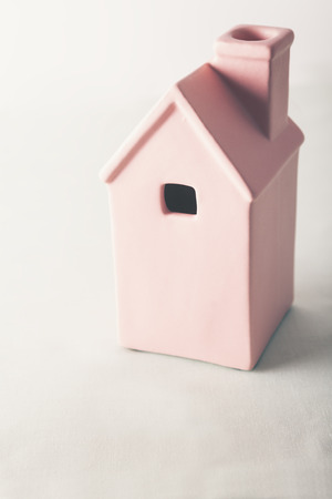 sold small: Toy pink house on pastel background with text space