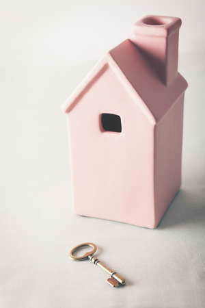 sold small: Toy pink house with gold key on pale pastel background Stock Photo