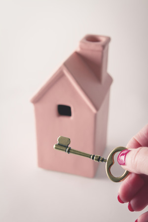 sold small: Toy pink house in background with hand holding key in front Stock Photo
