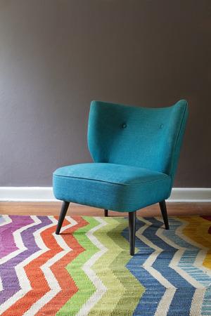 Interieur enkel wintertaling blauwe leunstoel en kleurrijke chevron patroon tapijt grijze muur