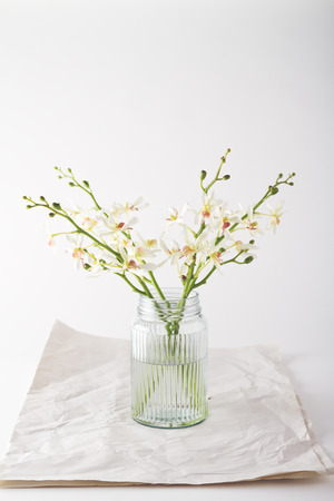 arrangements: Simple pure white orchids in a vintage glass jar with space for text