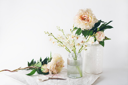 flowers in vase: Florist preparation with a selection of vases scissors and string horizontal