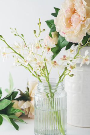 interior decor: Close up of white orchid flowers in a glass vase with roses in the background