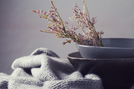 floristry: Still life gray vintage bowls with pink flowers and woolen scarf horizontal