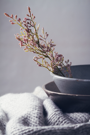 Still life gray vintage bowls with pink flowers and woolen scarf
