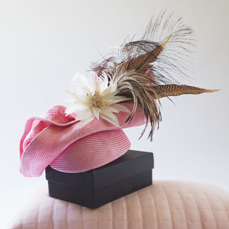 pink hat: Pink fashion races hat with flower and feathers on a bedroom pillow and box Stock Photo