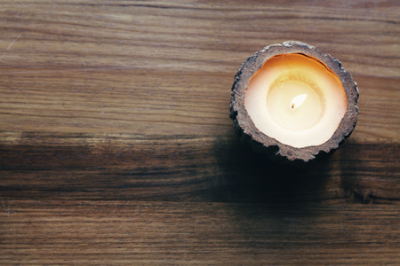 Overhead of a burning decorative candle on a wooden background