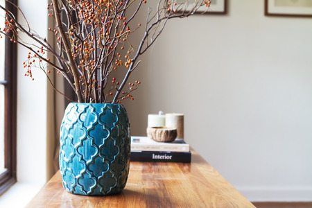 Horizontal moroccan teal vase with clear space for text on white wall in background