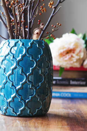 Close up of teal moroccan vase with sticks and background decor in home interior