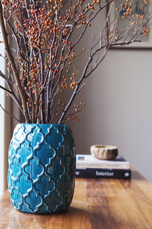 Teal blue moroccan vase with dried berry stick arrangement home interior Archivio Fotografico