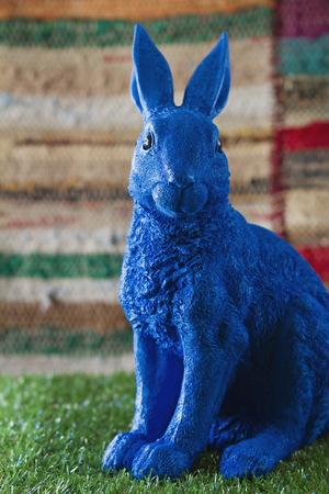 Blue easter bunny ornament on grass with textured background