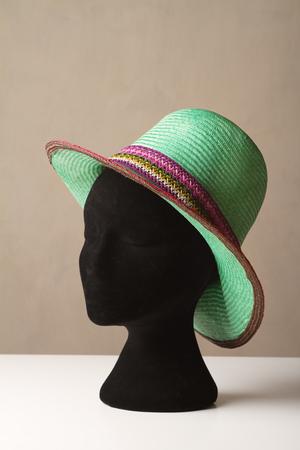 Ladies green fashion hat on display on a black hat block