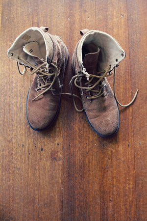 work boots: Overhead of worn old walking or work boots on rustic wooden floor